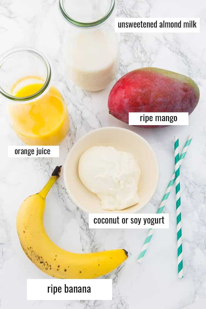 ingredients for a mango smoothie on a marble countertop with labels