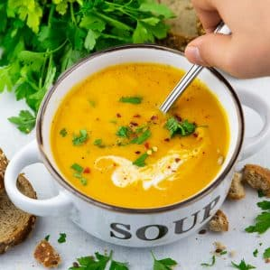 a bowl of vegan pumpkin soup with a hand holding a spoon
