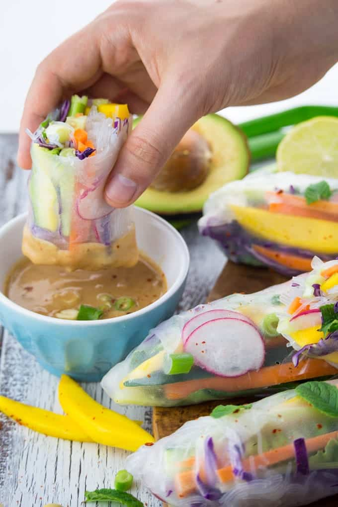 a hand dipping a rice paper roll into a bowl of peanut sauce