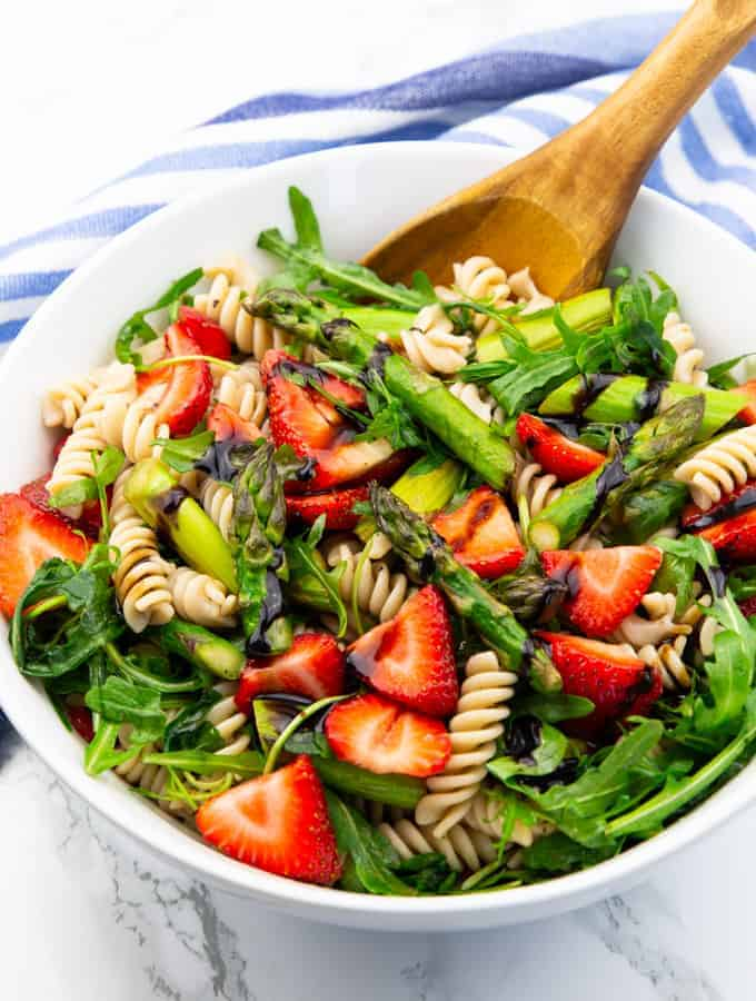 pasta salad with asparagus, strawberries, and arugula in a white bowl with a wooden spoon on a marble countertop
