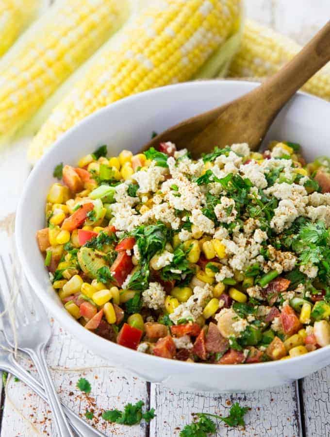 corn salad in a white bowl with a wooden spoon whit four corncobs in the background