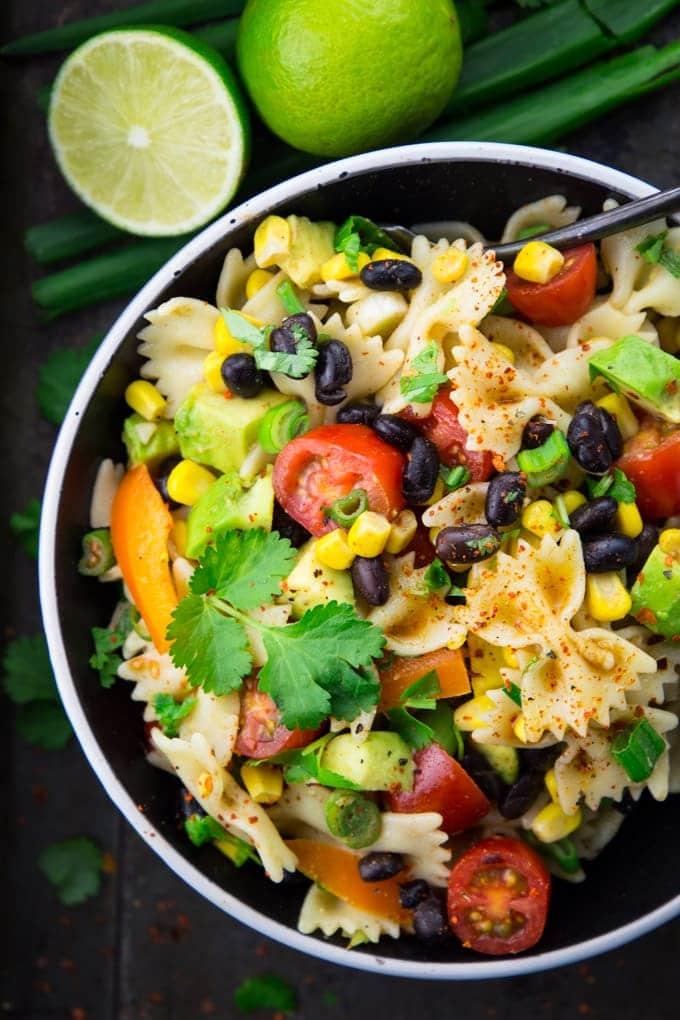 Mexican pasta salad with tomatoes, black beans, corn, and avocado in a black and white bowl with a spoon and two limes in the background