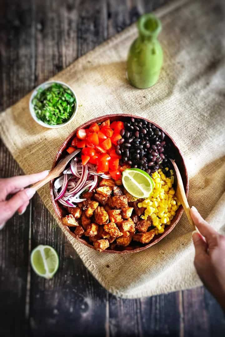 a bowl with Southwestern Salad with Chile Lime Tofu Nuggets on a wooden countertop with a lime and a bottle of dressing on the side