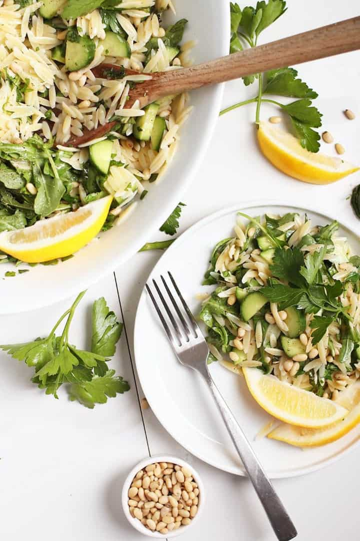 a white plate with lemon orzo salad with a fork and a large bowl with salad in the background
