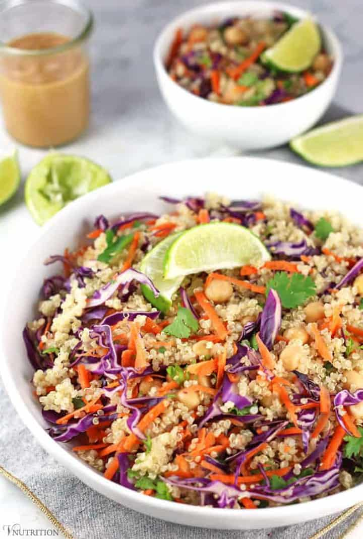 Thai quinoa salad with carrots and red cabbage in a white bowl with another smaller white bowl and limes as well as a glass of peanut dressing in the background
