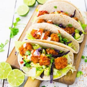Four vegan cauliflower tacos on a wodden board, ready to be served