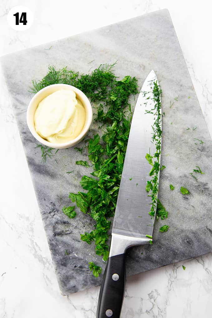 chopped parsley and dill on a cutting board with a knife