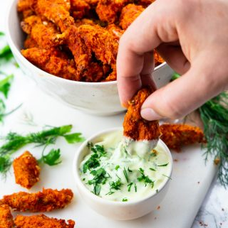 a hand dipping a vegan chicken finger into a small bowl of mayonnaise