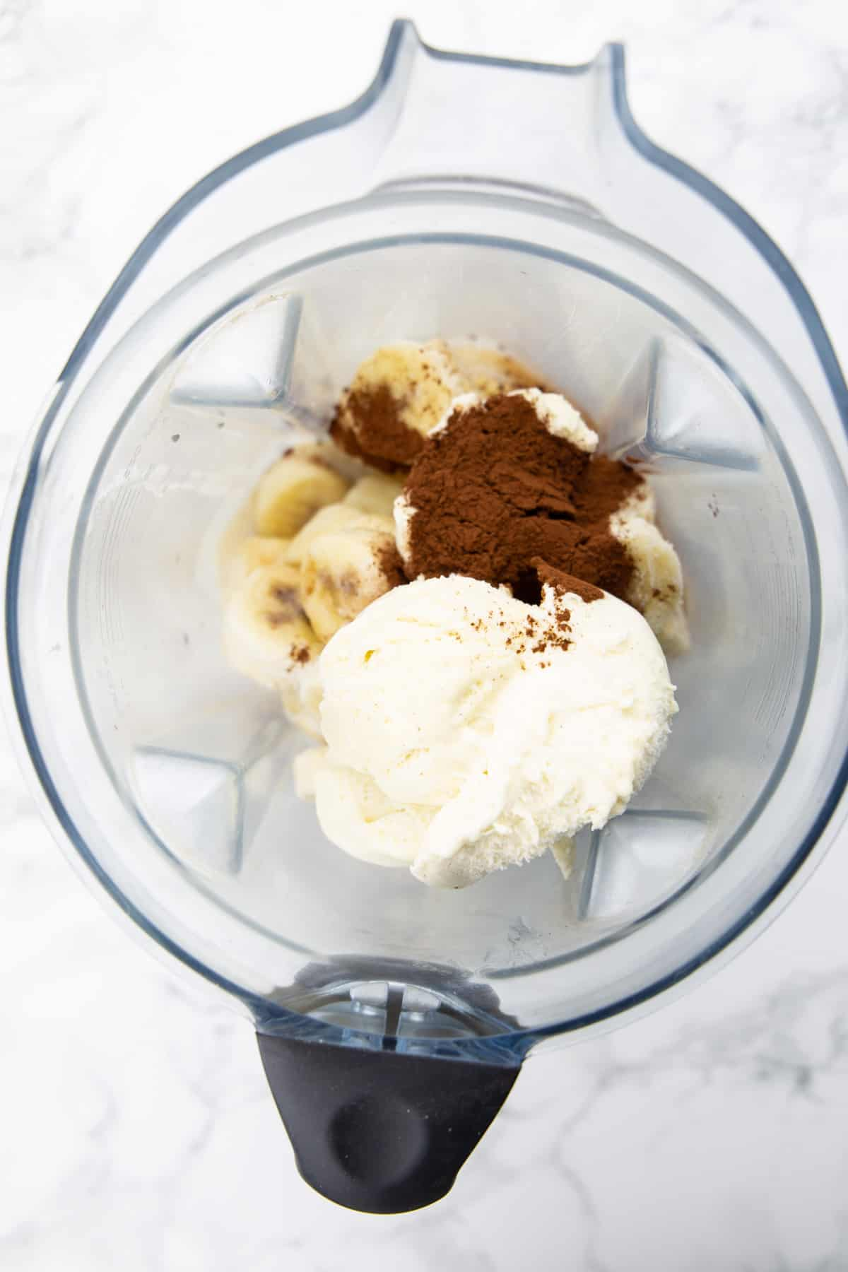 frozen bananas, cocoa powder, and ice cream in a blender