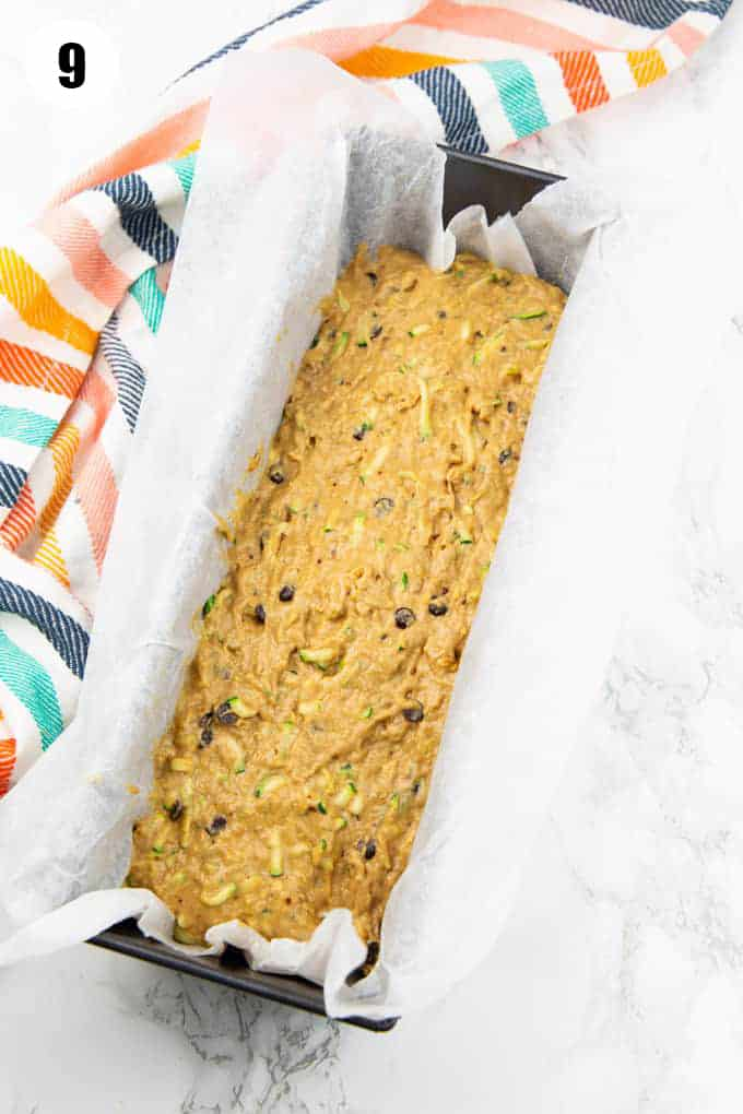 zucchini bread batter in a loaf form lined with parchment paper