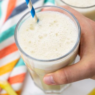 a hand holding a glass with banana milk and a blue straw
