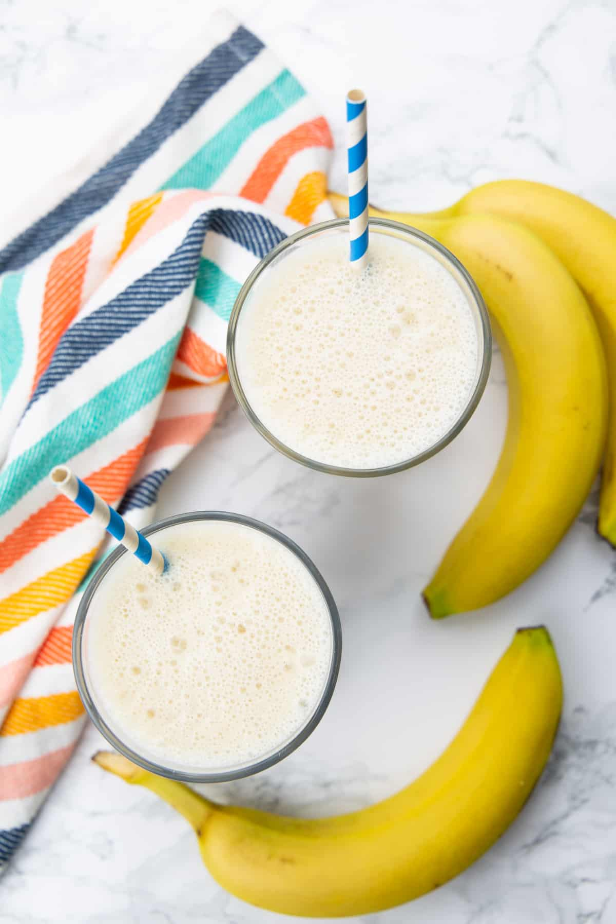 two glasses of banana milk on a marble countertop with bananas on the side