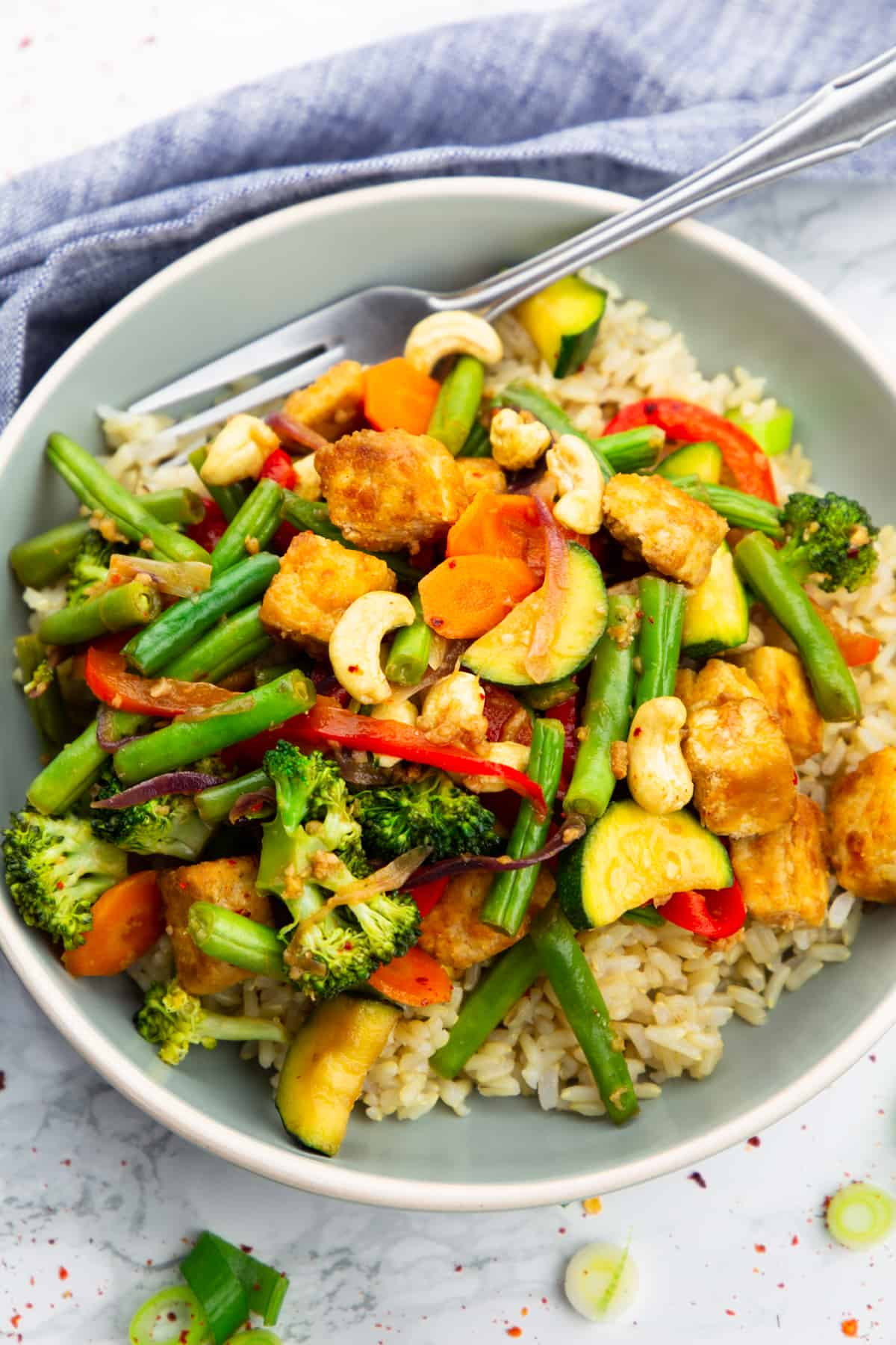 Tofu Stir Fry over brown rice in a grey plate with a fork