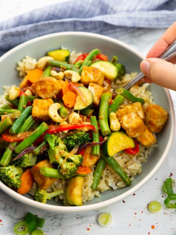 a grey bowl with brown rice and tofu stir fry with a hand holding a fork