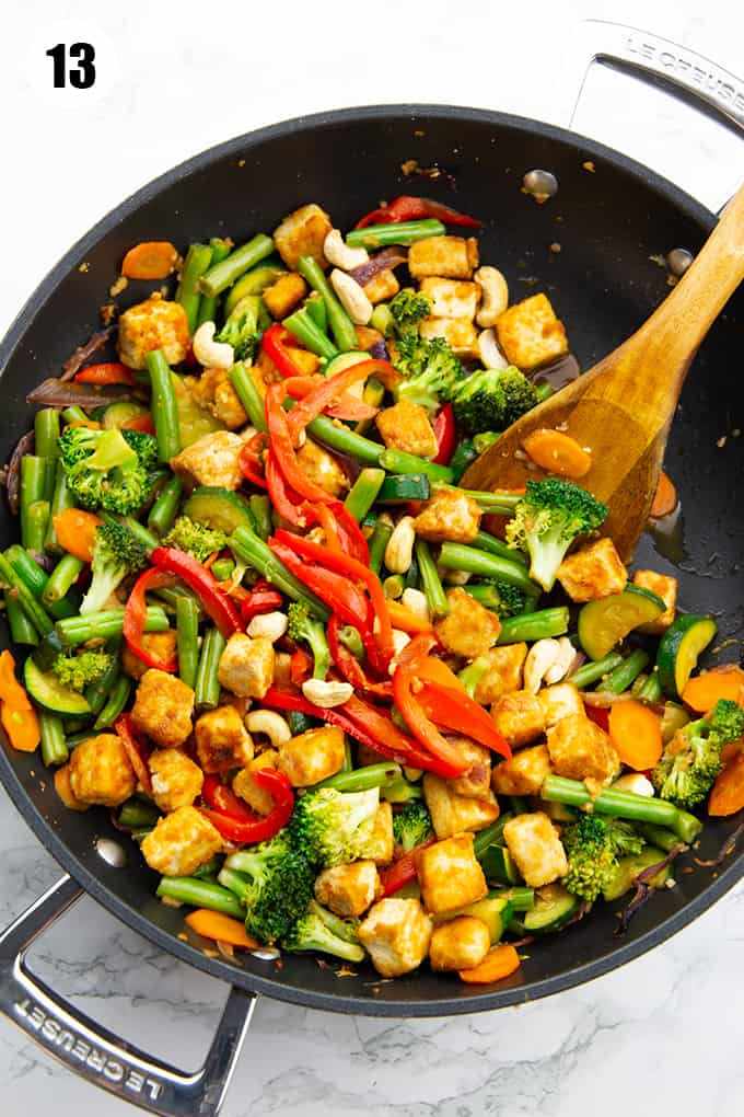 Tofu Stir Fry in a black pan with a wooden spoon on a marble countertop