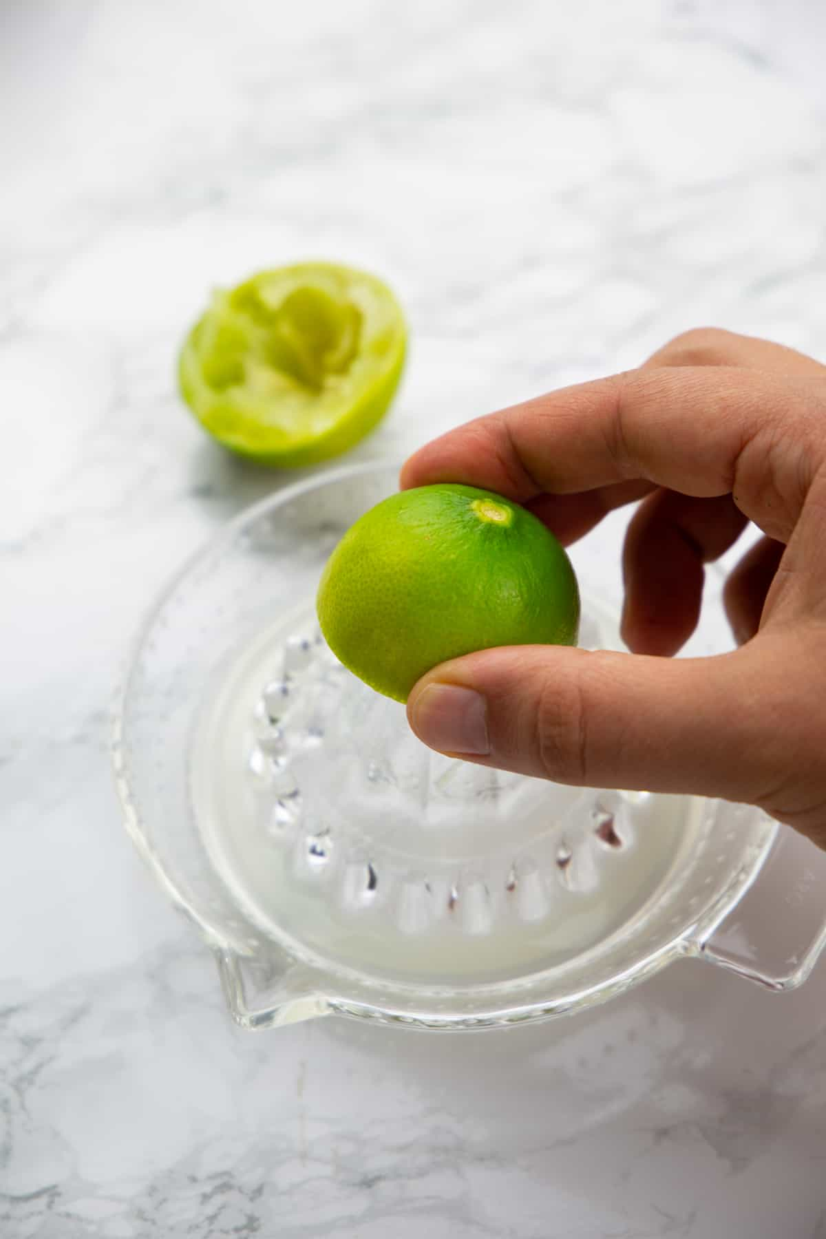 a hand juicing a lime with a lemon squeezer made of glass