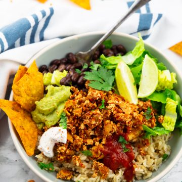 a grey bowl with brown rice, lettuce, guacamole, and sofritas with a fork