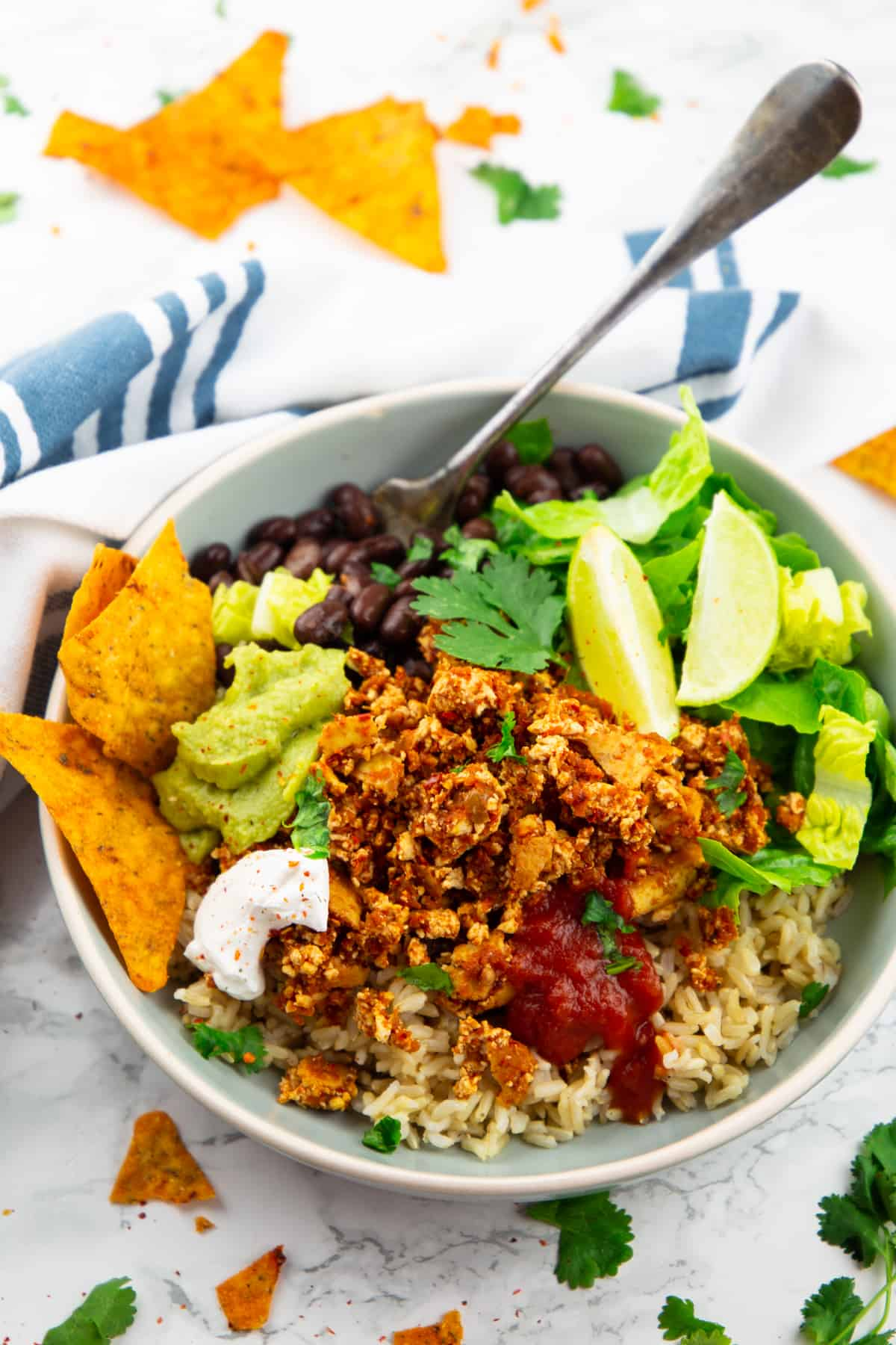 a gerat bowl with brown rice, lettuce, guacamole, and sofritas with a fork