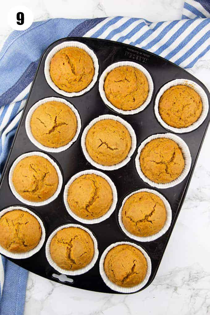12 vegan pumpkin muffins in a muffin pan on a marble countertop