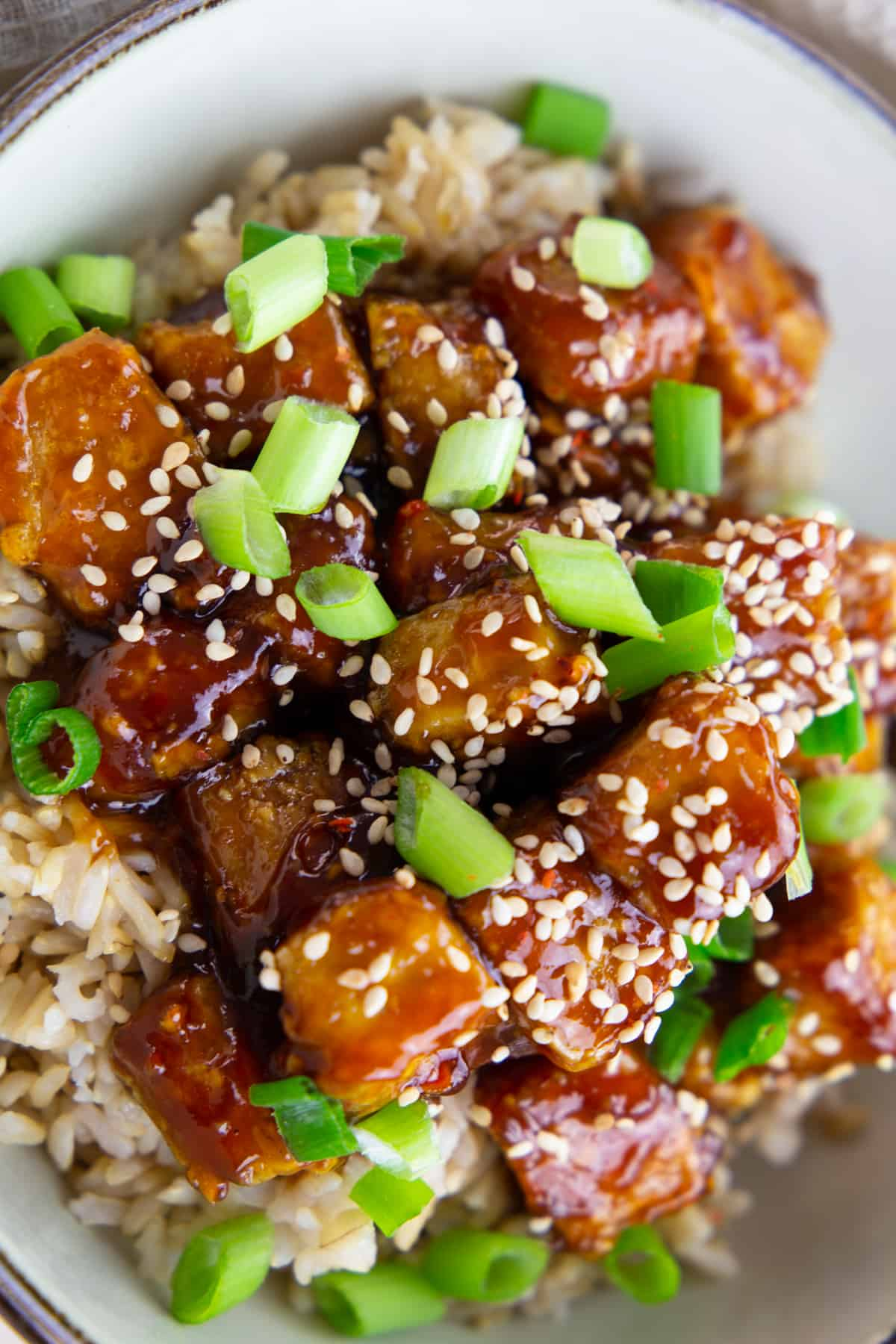 a close-up photo of baked tofu cubes with general tso sauce in white bowl