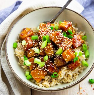 general tso tofu over rice sprinkled with sesame seeds and green onions in a grey bowl on a wooden board