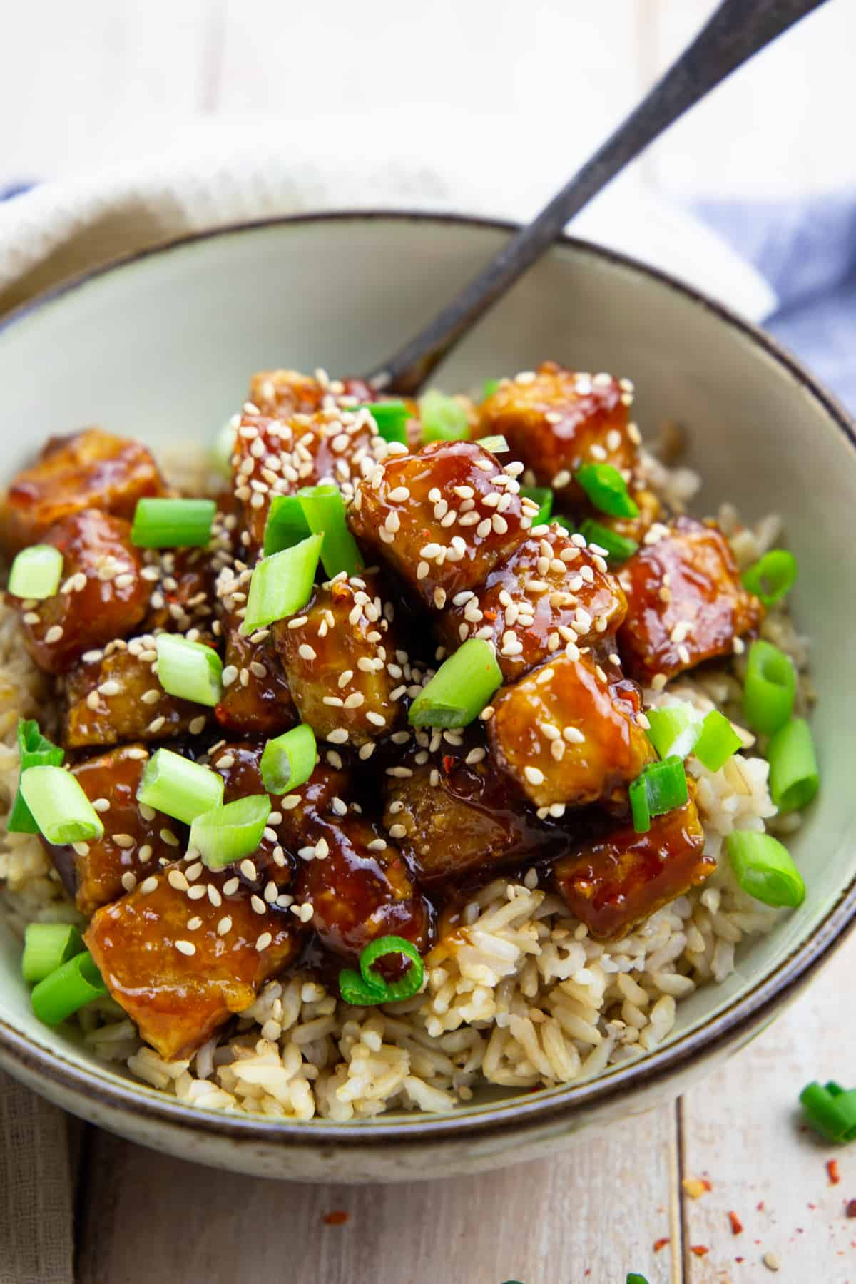 general tso tofu over rice sprinkled with sesame seeds and green onions in a grey bowl