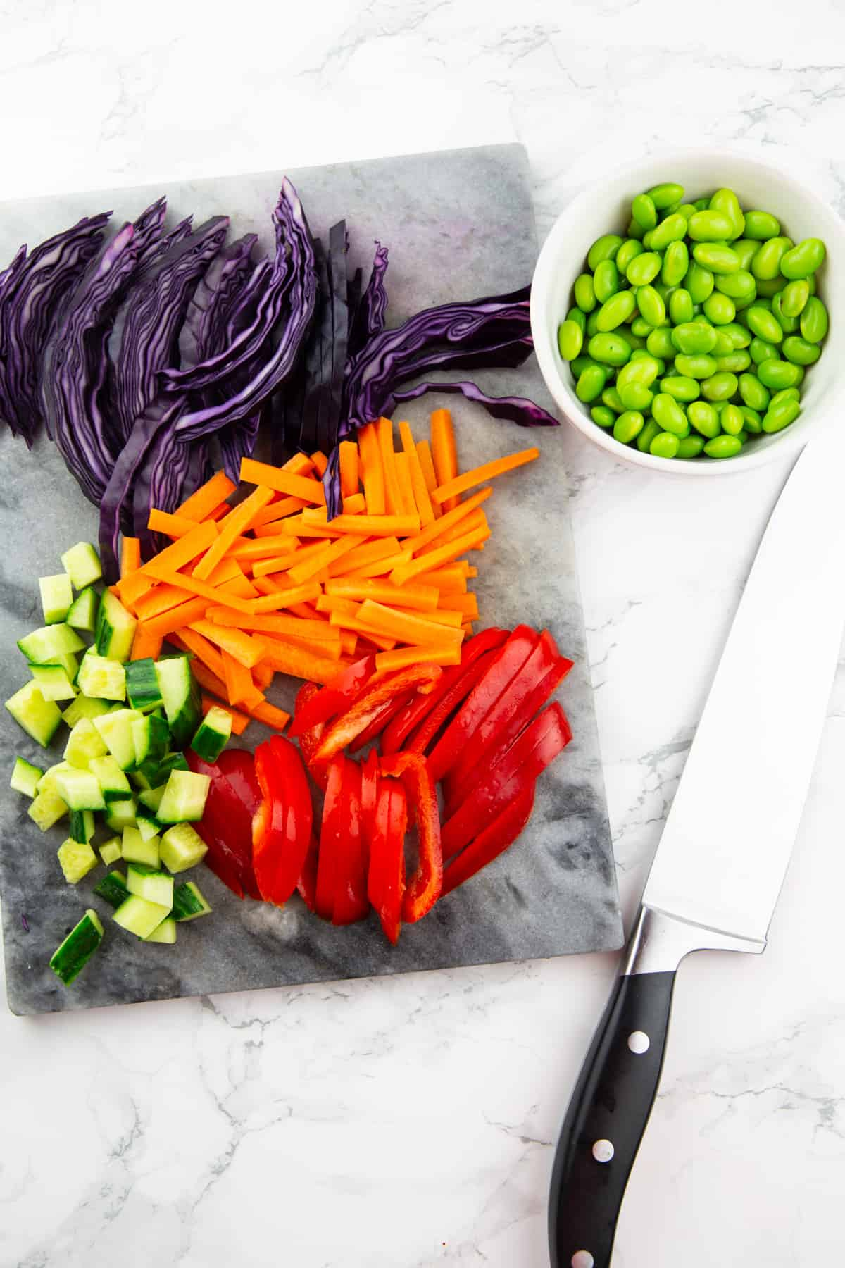 chopped up cucumber, bell pepper, carrots, and red cabbage on a cutting board