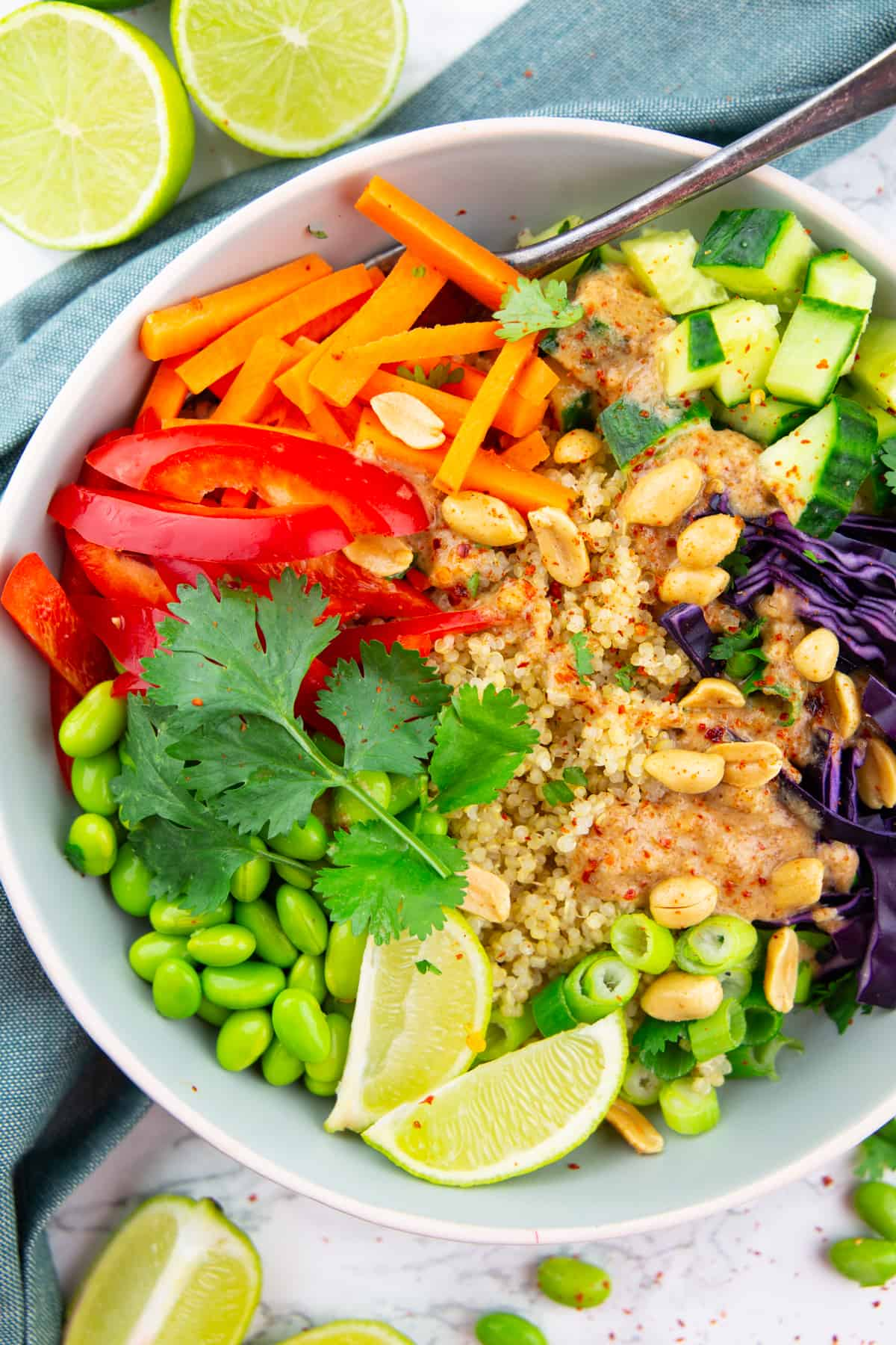 a grey bowl with quinoa, vegetables, cilantro, and lime on a blue dish cloth with a fork
