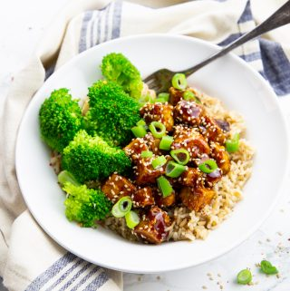 teriyaki tofu with brown rice and broccoli in a bowl on a marble countertop