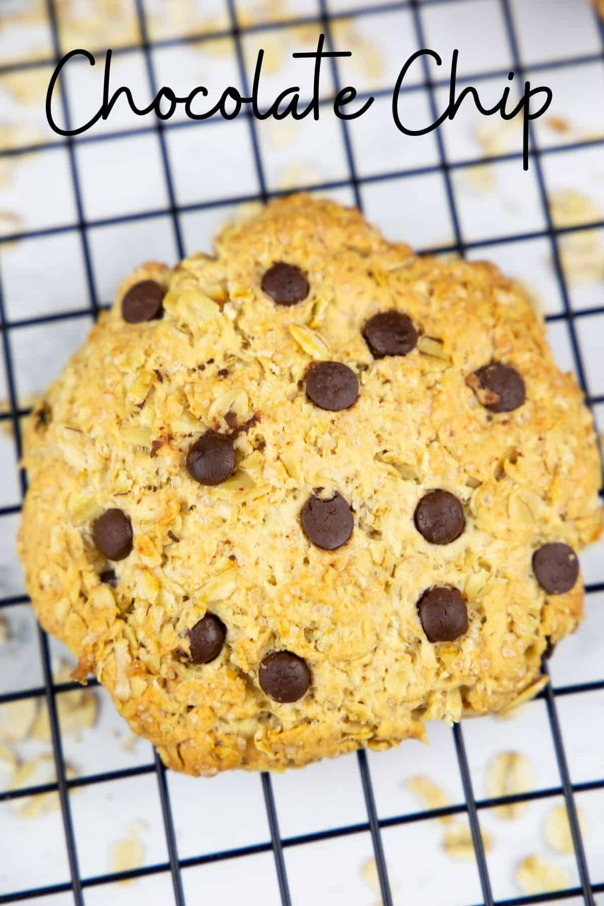 an oatmeal cookie with chocolate chips on a cooling rack