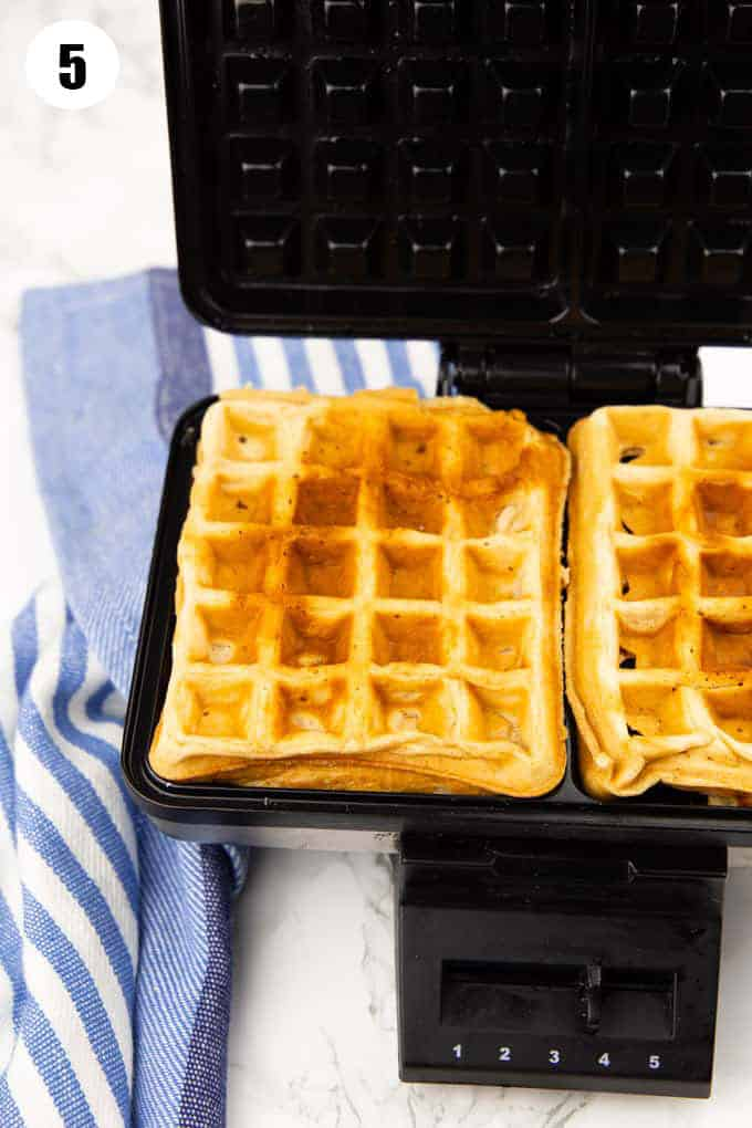 two waffles in a waffle maker on a marble countertop