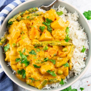 Vegetable korma with rice in a grey bowl on a marble countertop