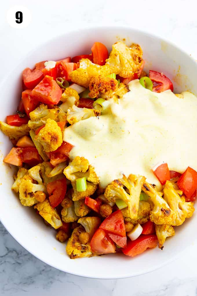 roasted cauliflower, chickpeas, and tomatoes in a white bowl with yogurt dressing