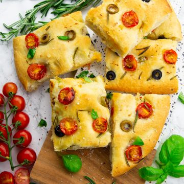 Focaccia squares on a wooden board with cherry tomatoes, rosemary, and basil on the side