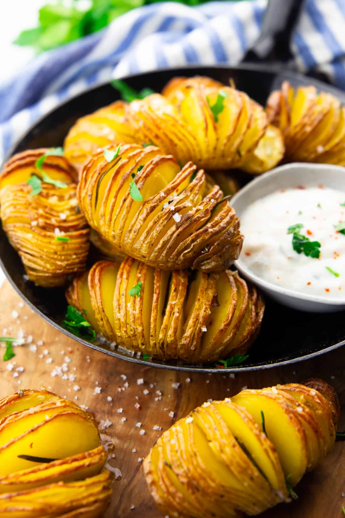 Hasselback Potatoes in a black pan with a small bowl of sour cream on the side