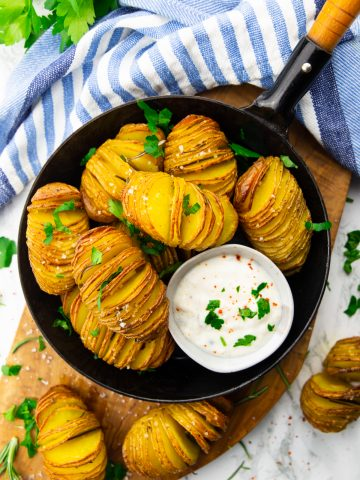 hasselback potatoes in a black pan on a wooden board with a small bowl of sour cream on the side