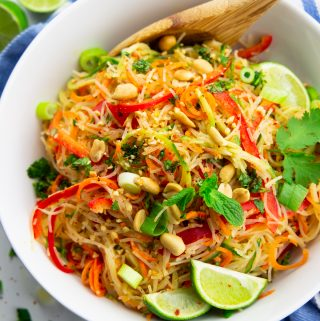 a bowl with noodle salad with spiralized vegetables and lime wedges on a marble countertop