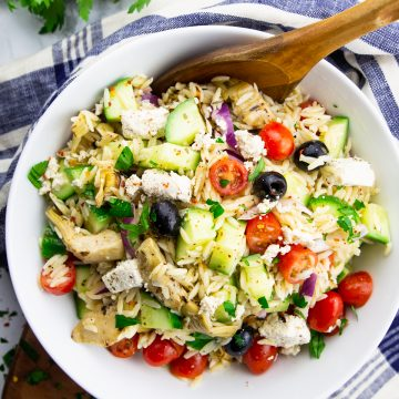 orzo pasta salad in a white bowl with a wooden spoon on a marble countertop