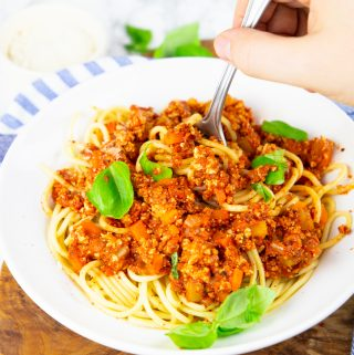 a hand with a fork picking up spaghetti with vegan bolognese out of a white bowl