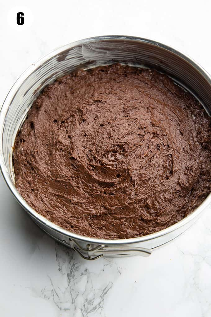 vegan chocolate cake batter in a springform pan on a marble countertop