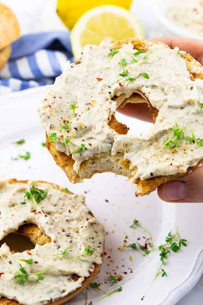 uma mão segurando um bagel com cream cheese vegan e um segundo bagel em um prato branco
