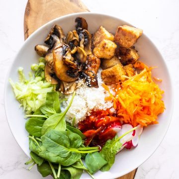 a bowl with bibimbap with tofu on a wooden board on a marble countertop