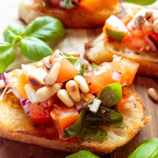 three bruschettas topped with roasted pine nuts on a wooden board with basil on the side