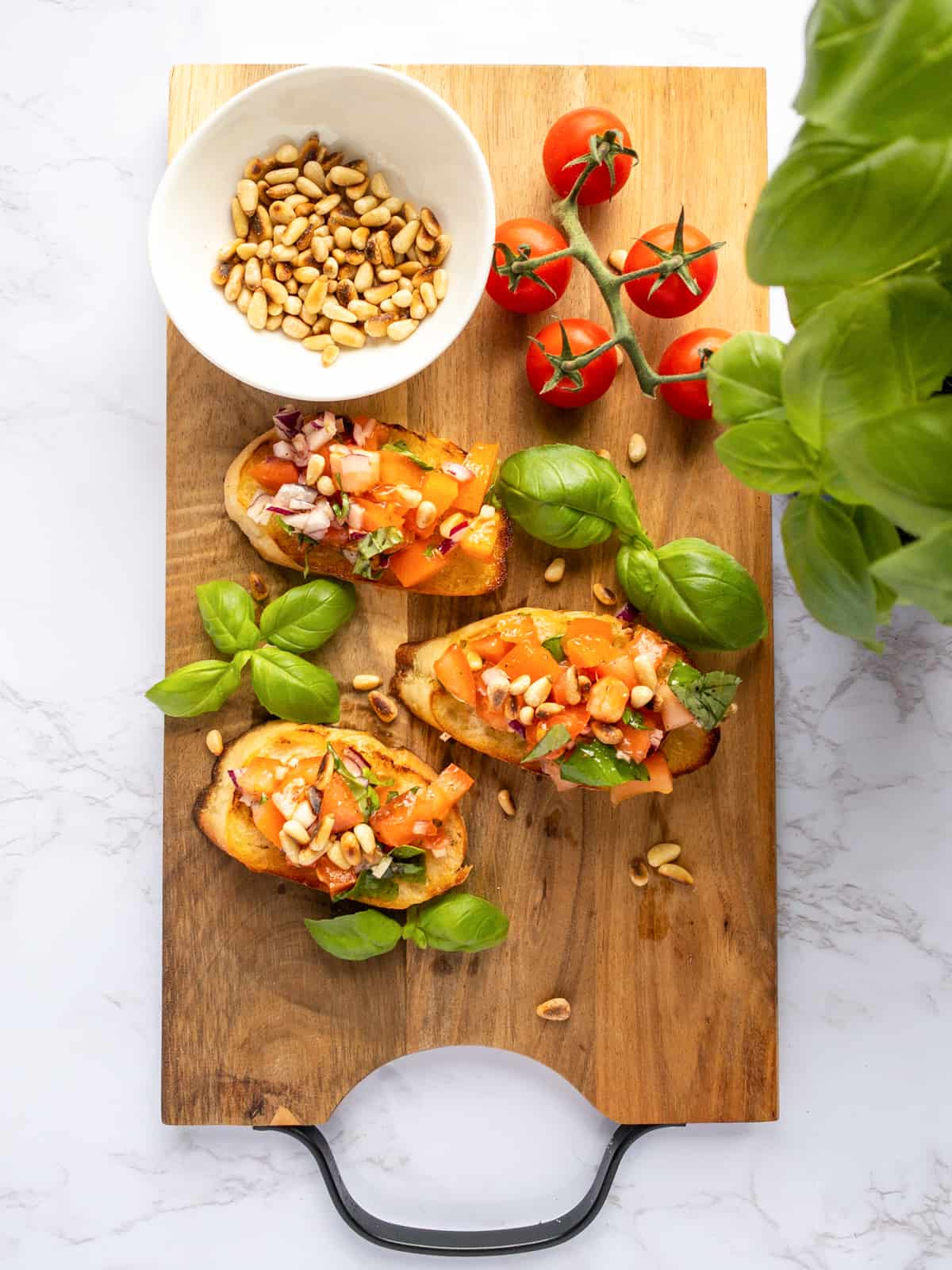 three bruschetta on a wooden cutting board with basil, pine nuts, and tomatoes on the side