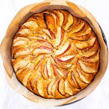 a freshly baked vegan apple cake in a baking pan lined with parchment paper