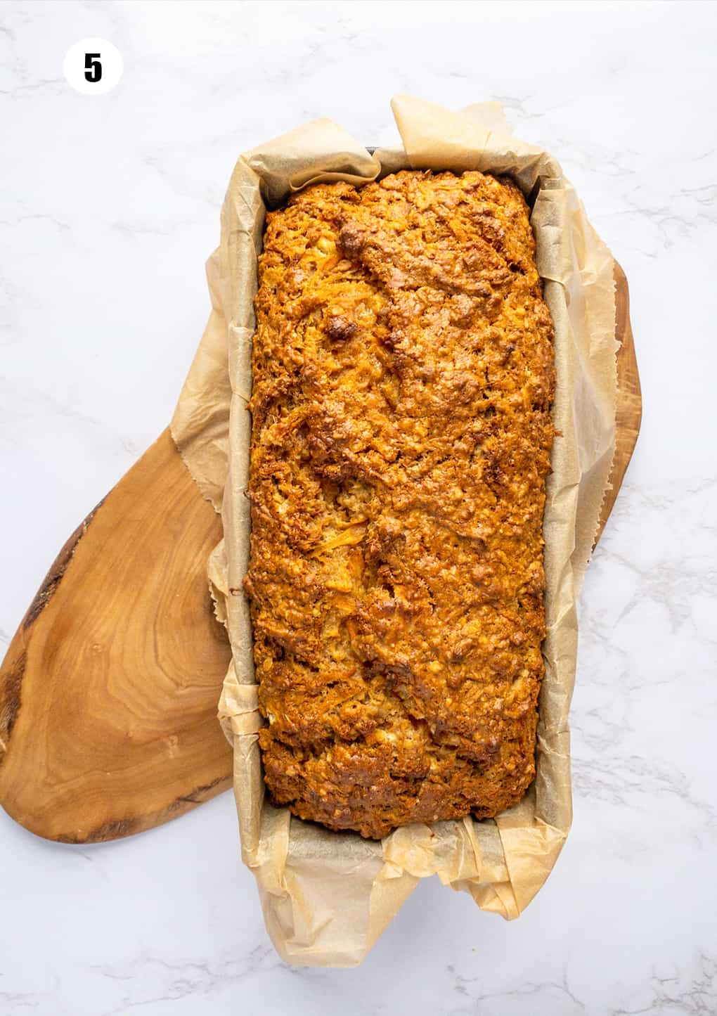 a vegan carrot cake in a loaf pan lined with parchment paper on a marble countertop
