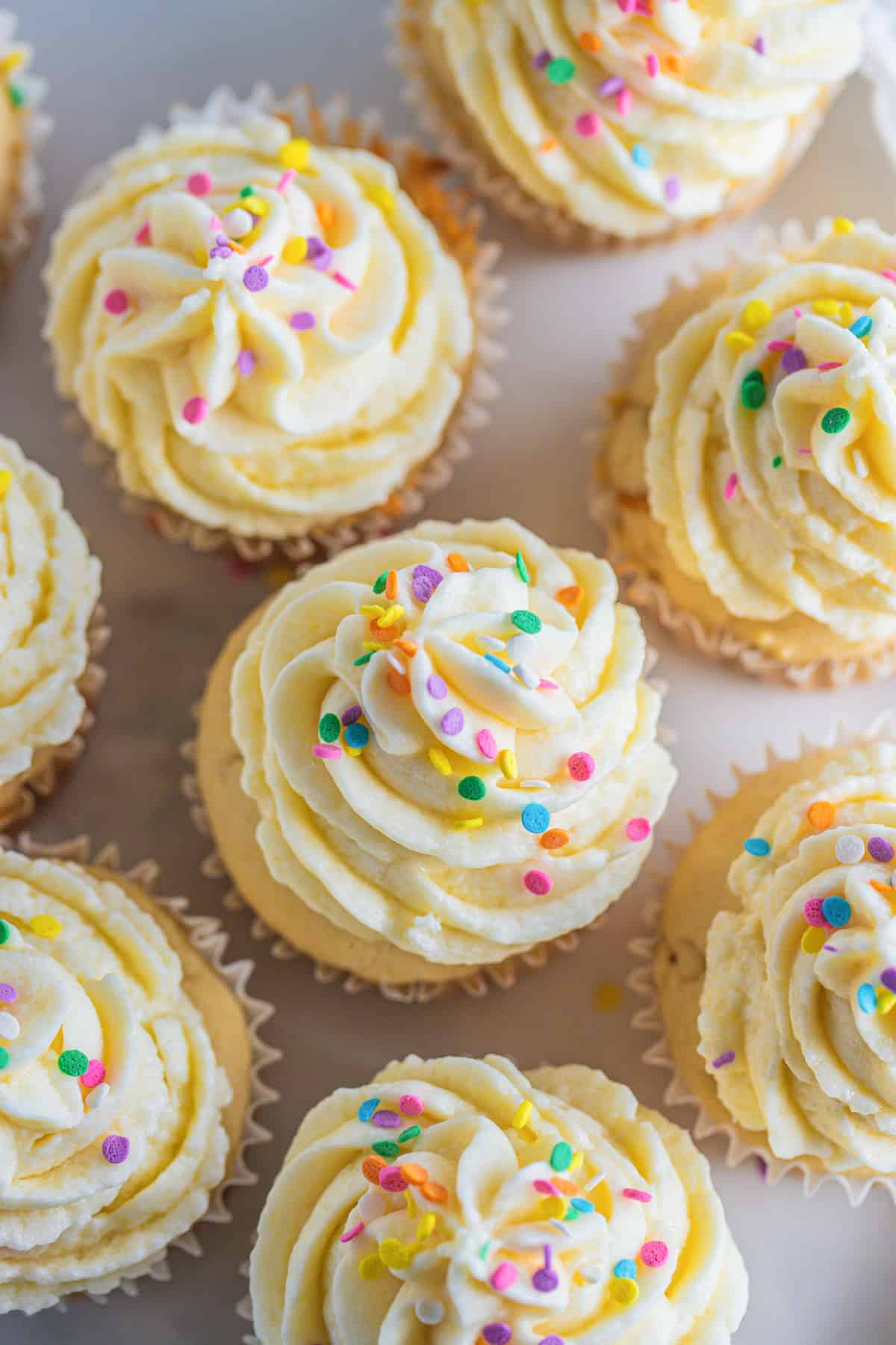 an overhead shot of vegan vanilla cupcakes with sprinkles