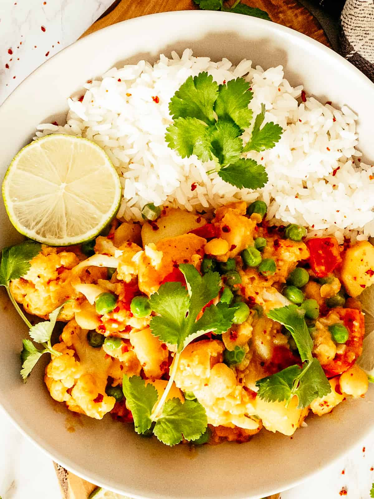 a close-up photo of cauliflower curry in a white bowl with cilantro sprinkled on top