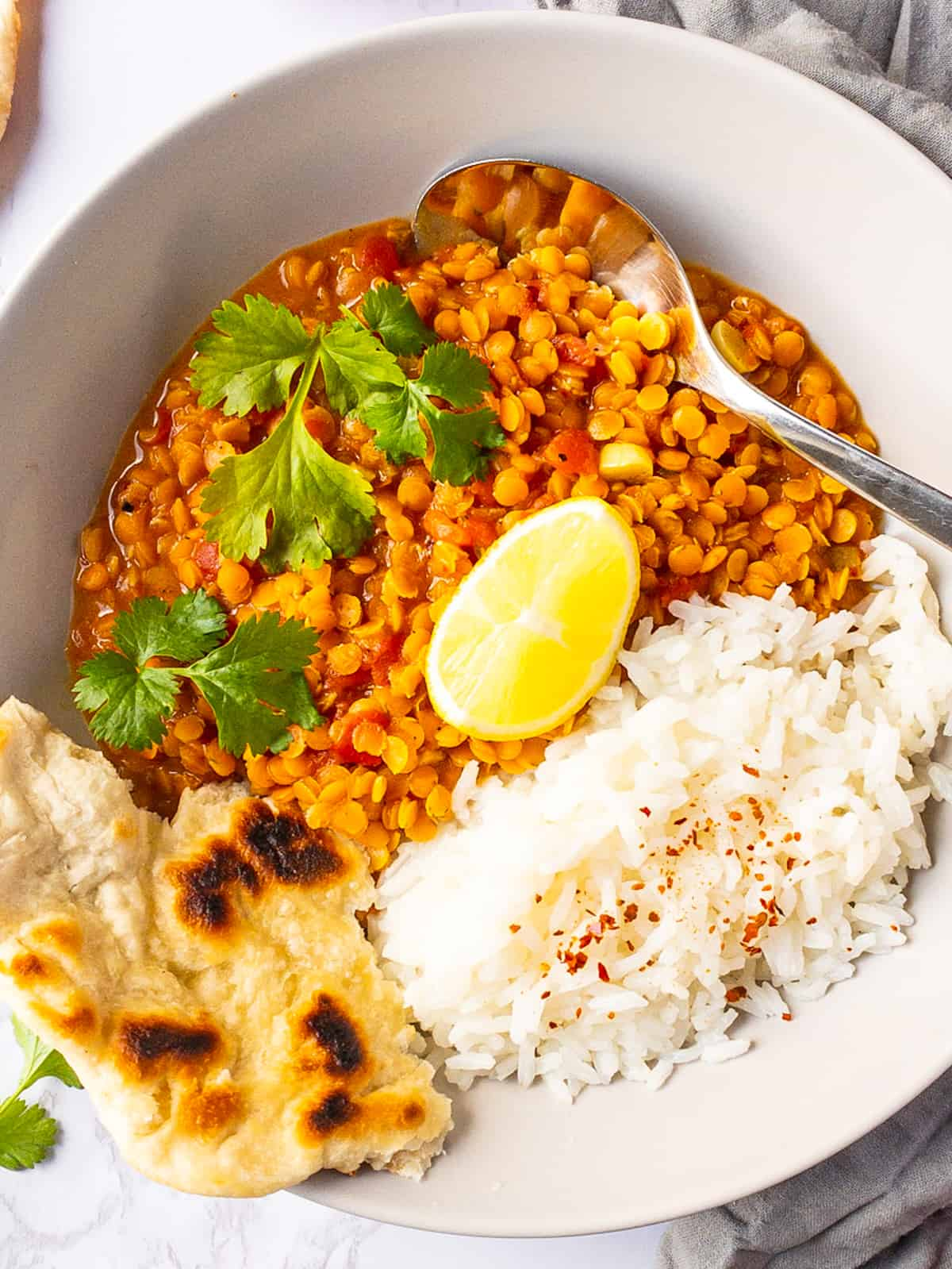 close-up of a red lentil dal with rice, naan bread, and fresh cilantro in a white bowl