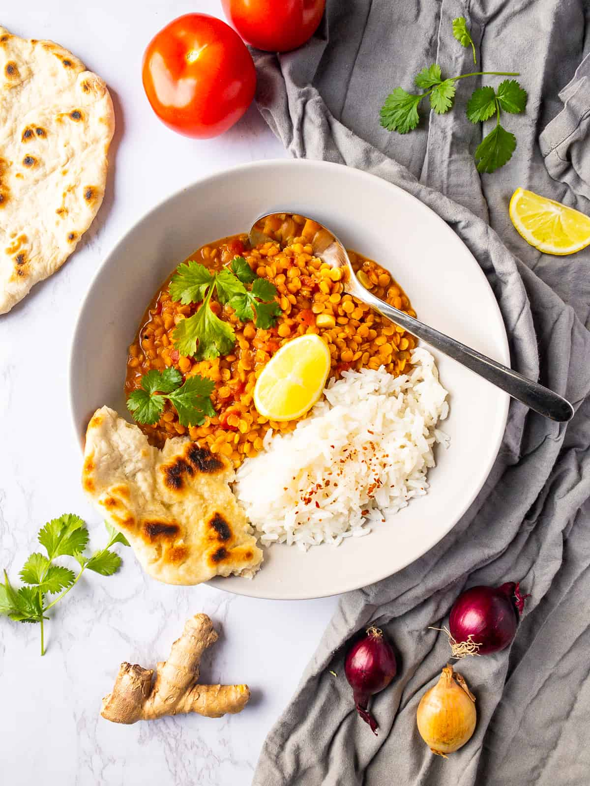 red lentil dal in a white bowl with rice and naan bread on the side